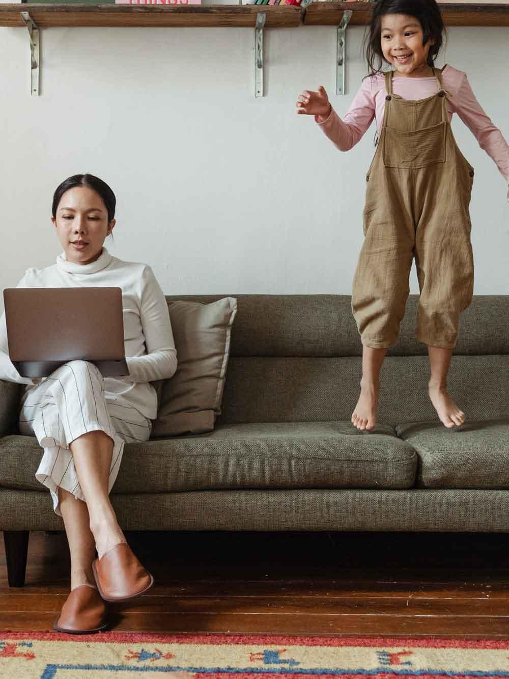 Frau_sitzt_mit_Laptop_auf_sofa_Kind_springt_auf_sofa