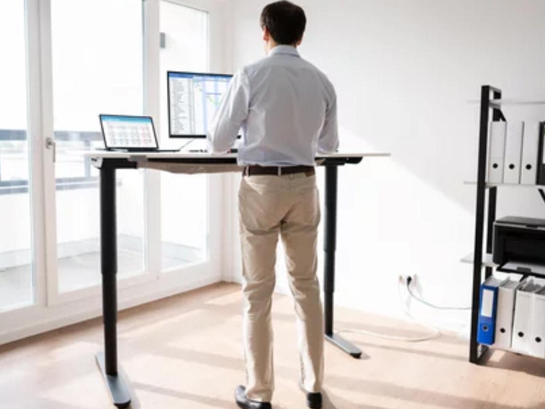 Mann arbeitet an elektrisch höhenverstellbarem Schreibtisch