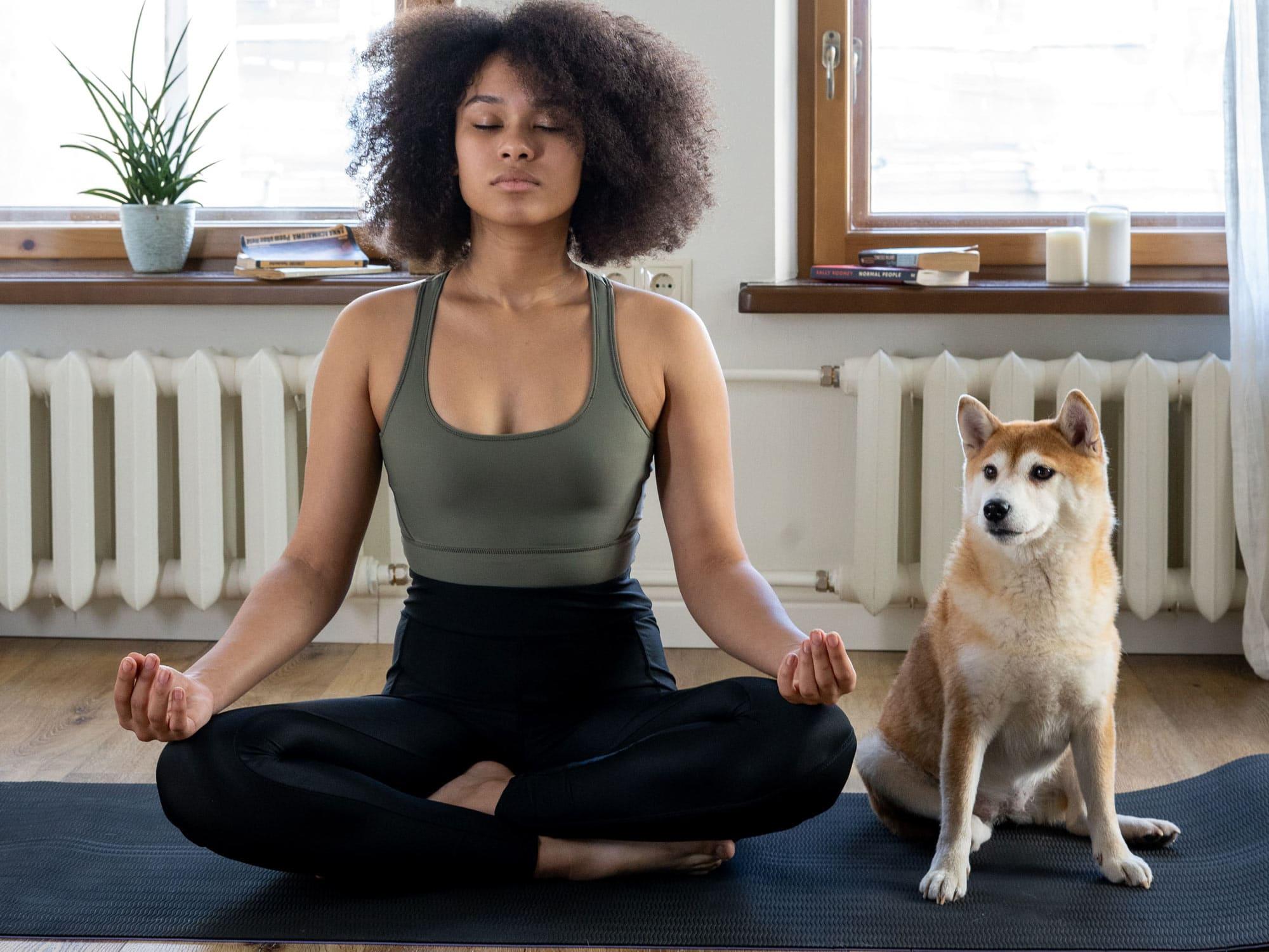 Frau_im_Schneidersitz_sitzt_neben_ihrem_Hund_auf_einer_Fitnessmatte - Zuhause