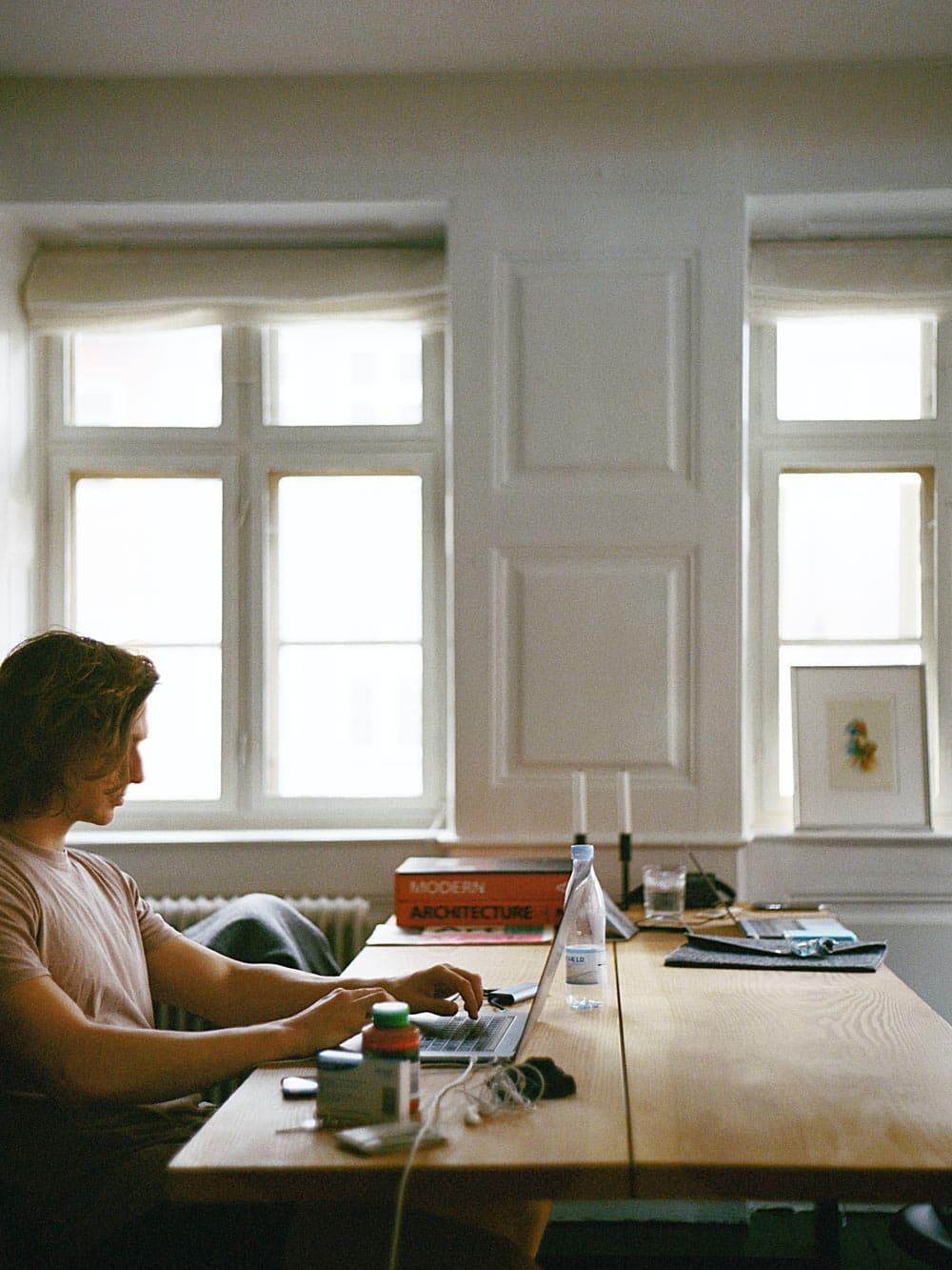 Mann_am_Schreibtisch_mit_Laptop