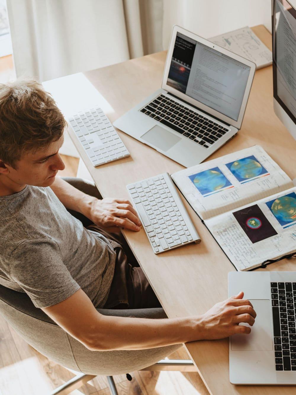 Mann_im_Home-Office_sitzt_vor_dem_laptop_und_einem_Bildschirm