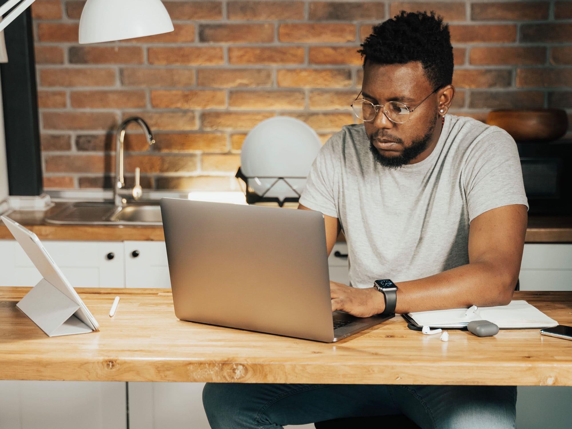 Mann_im_Home-Office - vor_ihm _steht _ein _Laptop _auf _dem _Schreibtisch