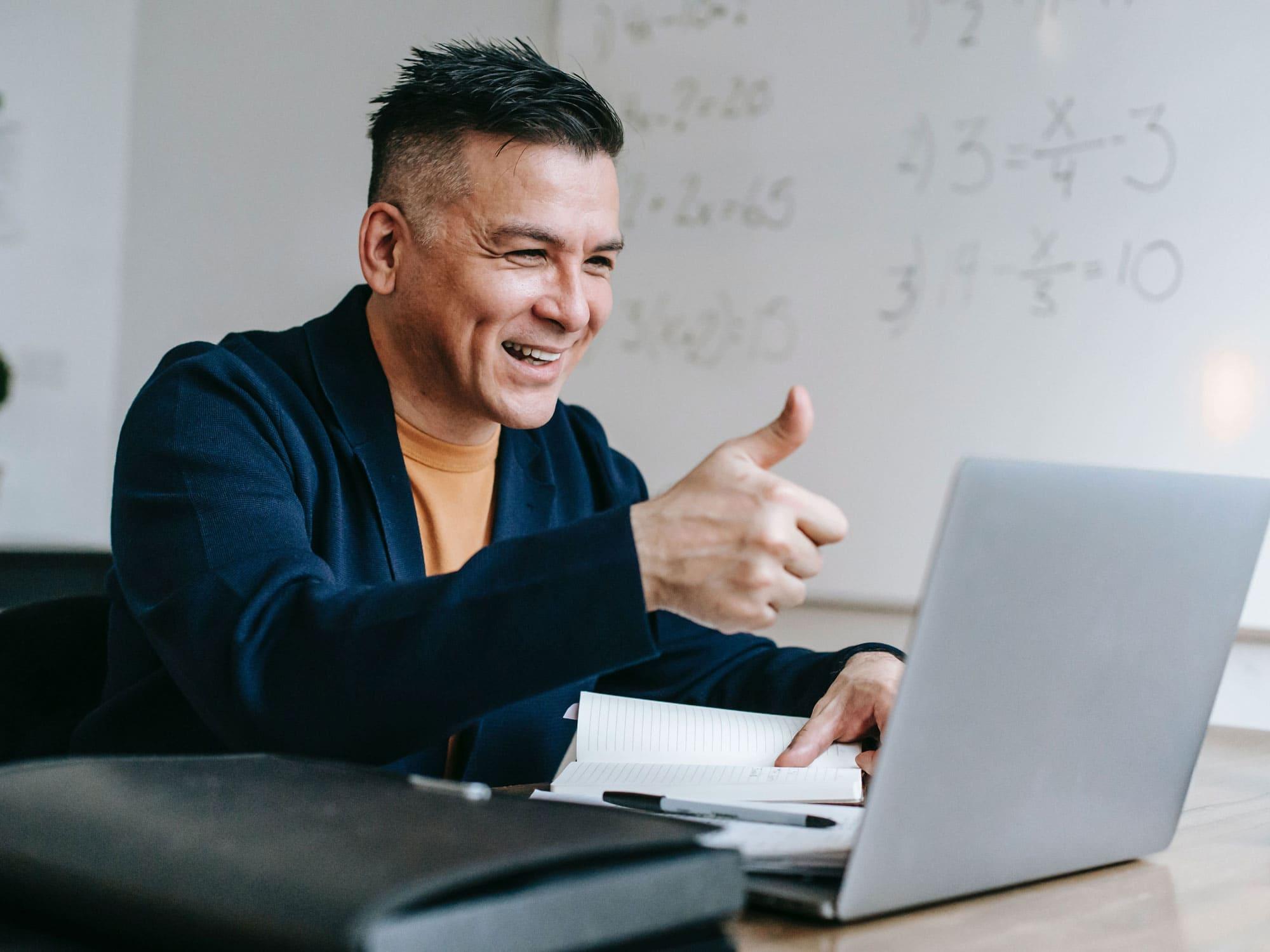 Mann_im_Home-Office_sitzt_am_Schreibtisch_vor_seinem_Laptop_und_hebt_einen_Daumen
