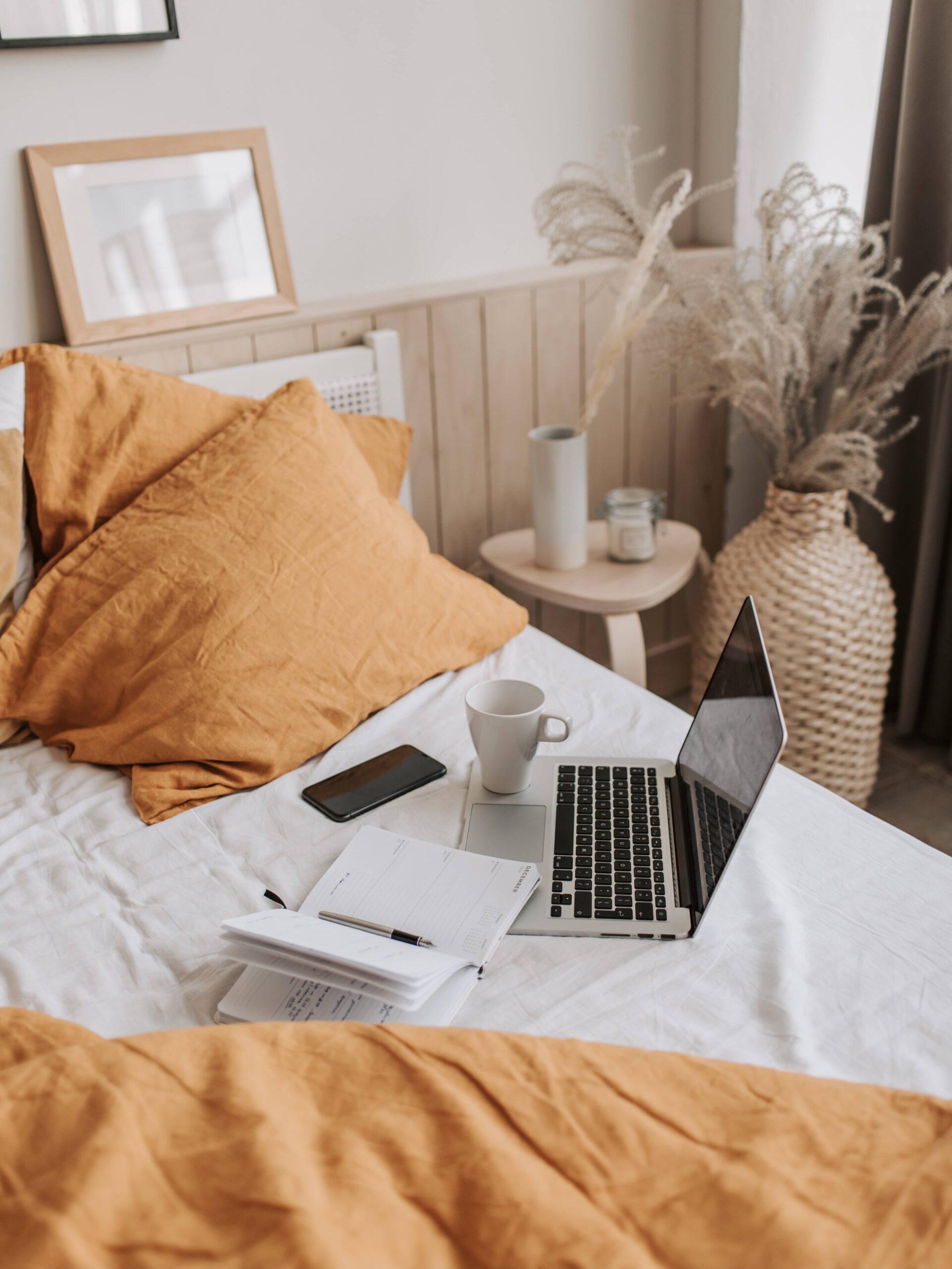 Computer_auf_Bett_mit_Handy_und_Notizzettel