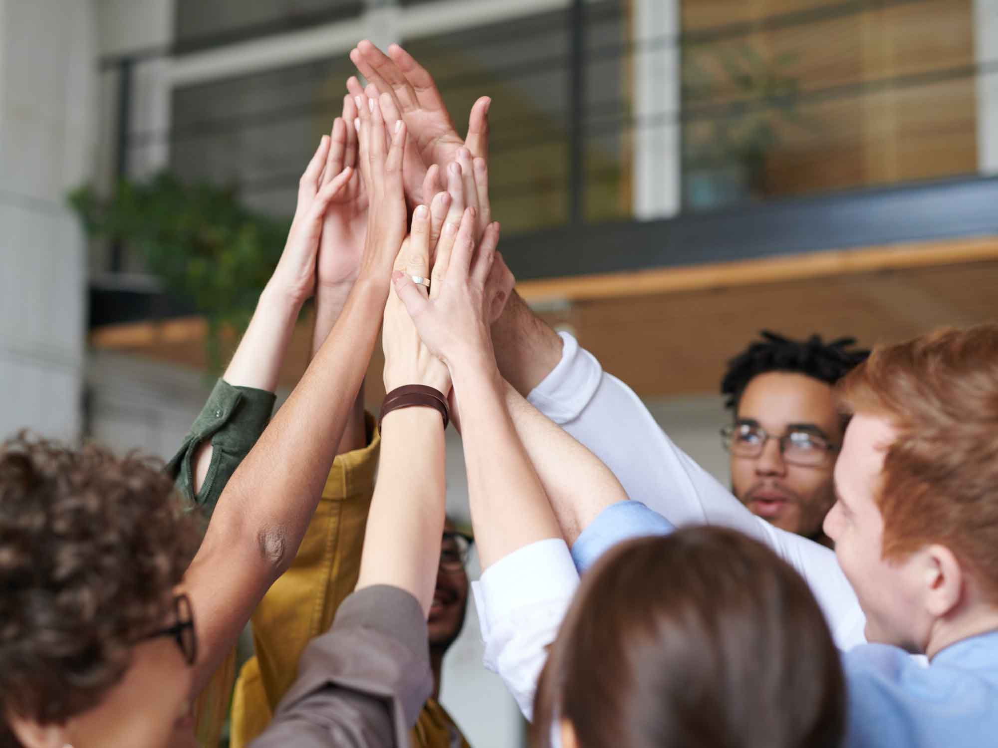 teamwork_arbeitstrend_wichtig_Gruppe_klatscht_hände_in_der_mitte_zusammen